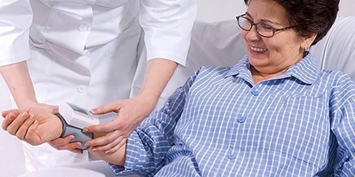 Врач проверяет давление больной гипертонией